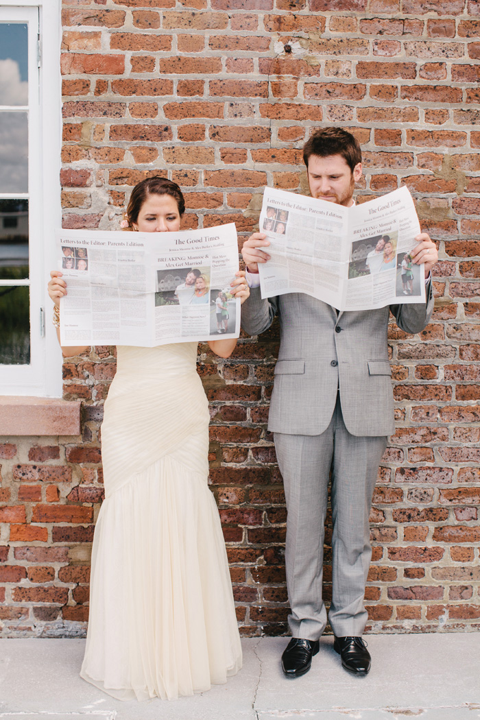 Bride and groom holding newspaper program | Riverland Photography | As seen on TodaysBride.com