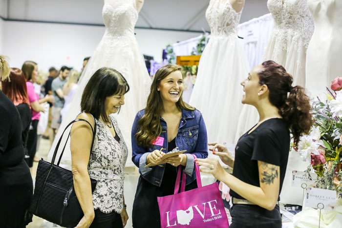 Girl talking to vendor with wedding dresses at Bridal Show | As seen on TodaysBride.com