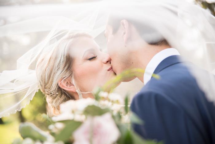 Bride and groom kissing under a veil   Sabrina Hall Photography   As seen on TodaysBride.com