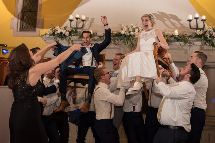 Bride and Groom being hoisted on chairs   Sabrina Hall Photography   as seen on Todaysbride.com