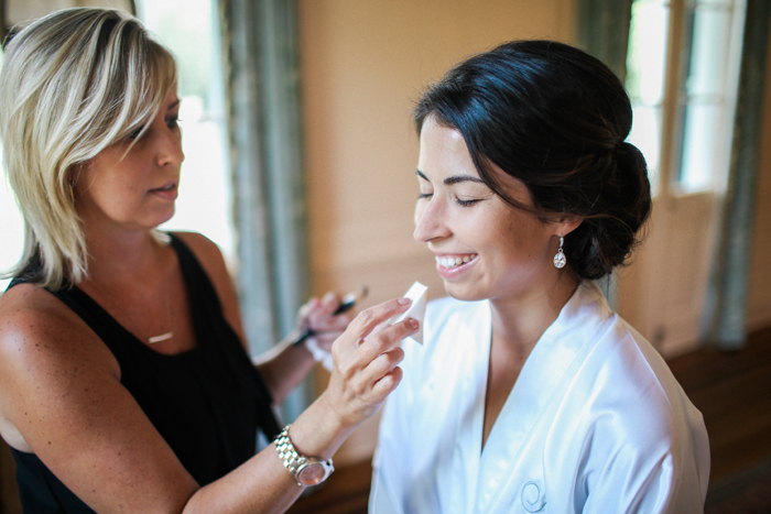 Woman applying makeup to a bride | Gideon Photography | as seen on TodaysBride.com