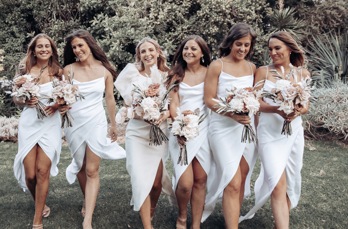 Bride and bridesmaids in white dresses with bouquets